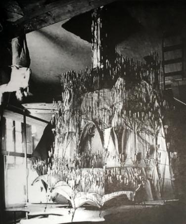 Fotografía en el estudio de Gaudí con un ensayo de catenarias para la formulación de la cúpula estereofunicular (posición normal e invertida) de la iglesia de la colonia Güell, elaborado para calcular las cargas y fuerzas del edificio a proyectar.